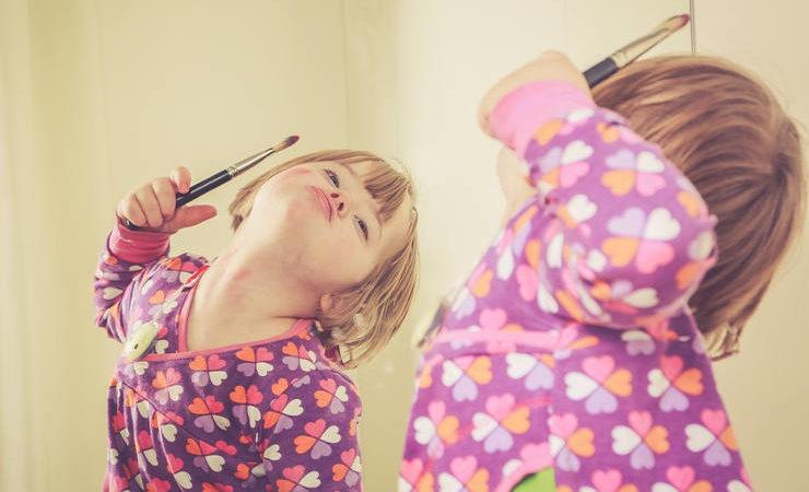 petite fille porteuse de la trisomie 21 se regardant dans un miroir