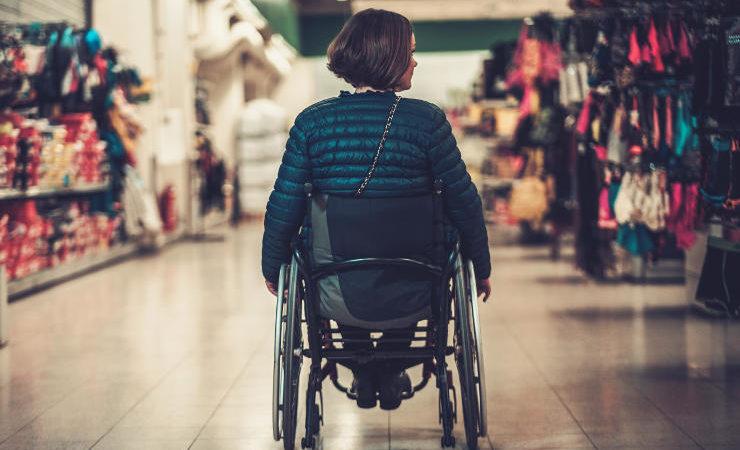 personne en fauteuil dans un magasin
