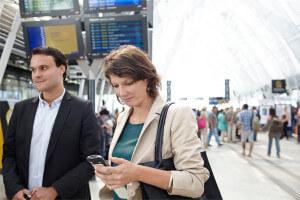 Voyageur utilisant une application de guidage sur smartphone dans une gare