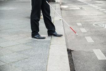 personne déficiente visuelle qui traverse la rue avec sa canne blanche