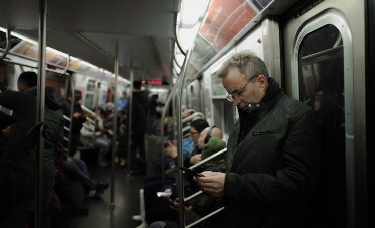 Usager regardant son portable dans un métro