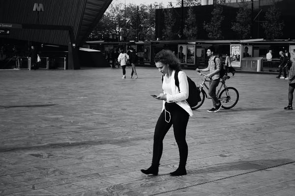 Femme qui marche en regardant son smartphone
