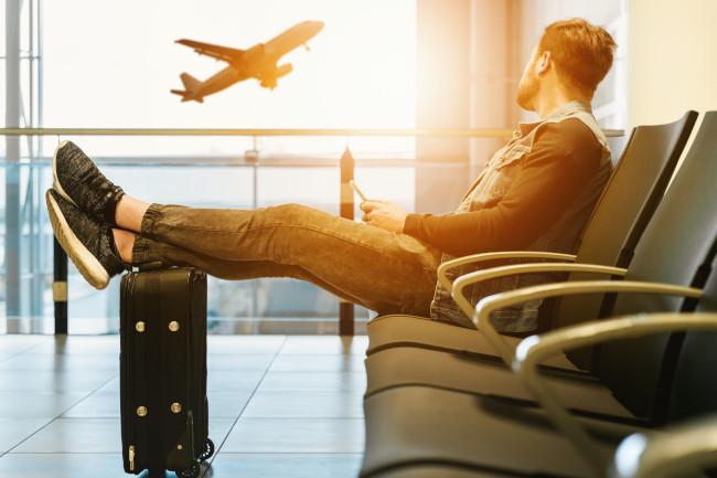une personne assise dans un aéroport et regardant un avion décoller