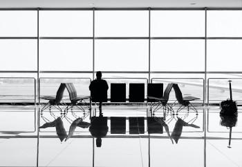 une personne de dos assise dans un aéroport