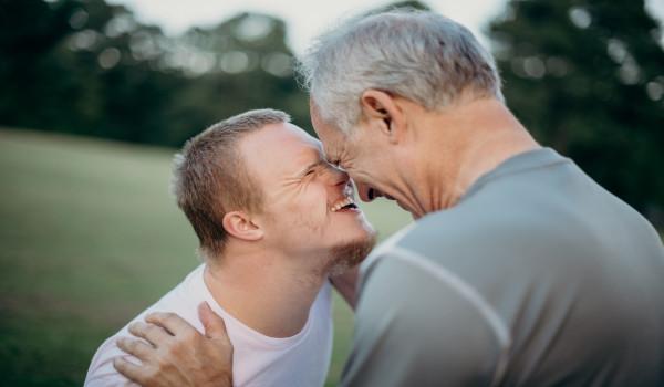 Un homme avec un handicap mental et son accompagnant se sourient