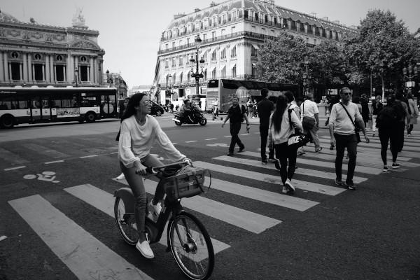 Des piétons et une cycliste se croisent à un carrefour
