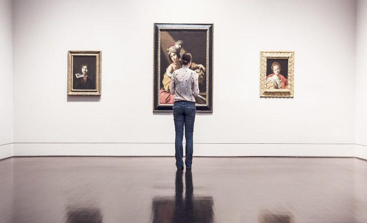 Une femme observe trois peintures dans un musée