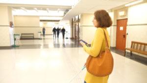 Une femme déficiente visuelle utilise Evelity pour se guider dans un lieu