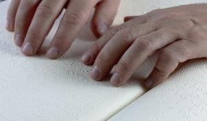 Une personne lit un livre en braille