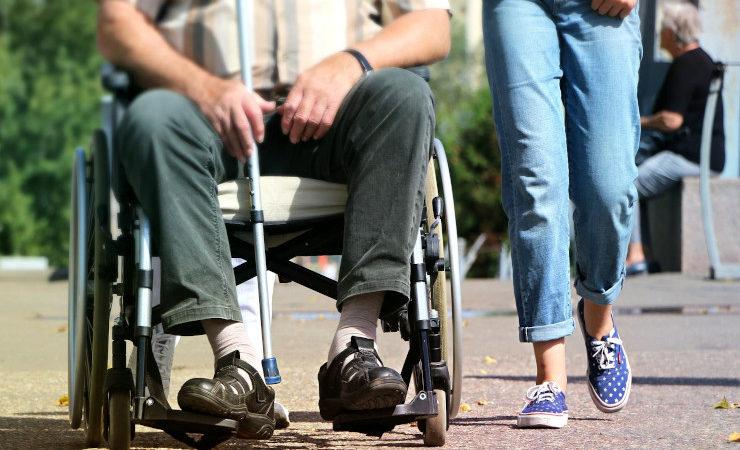 Personne en fauteuil roulant et son accompagnatrice
